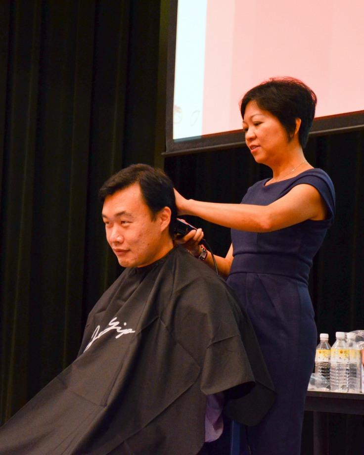 Mrs Lim shaving Mr Tan Boon Poh's locks at Hair For Hope 2012