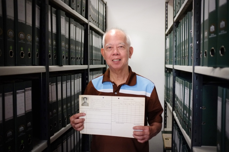 Mr Siu holding his Student Life Card. The green files contain Student Life Cards he had filed and indexed for the RAM